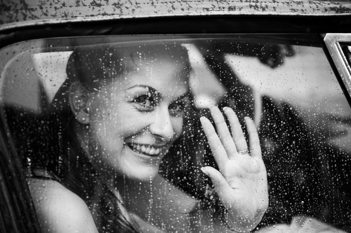 Bride waving in car